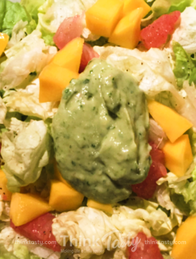 Green salad with grapefruit and mango topped with avocado dressing
