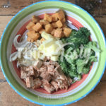 All sorts of flavors and textures in this bowl filled with season tofu, caramelized onions, roasted sweet potato and broccoli and topped with pineapple