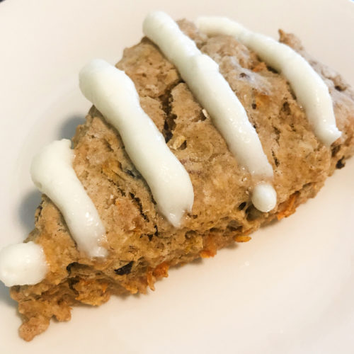 Homemade scone filled with carrots, raisins, and pecans topped with cream cheese frosting