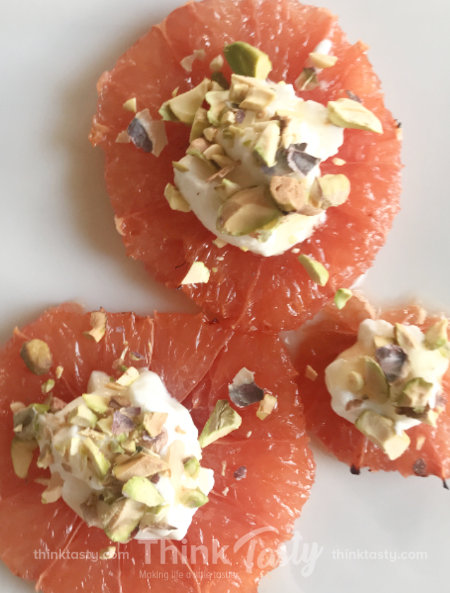 Grapefruit slices topped with yogurt and pistachios