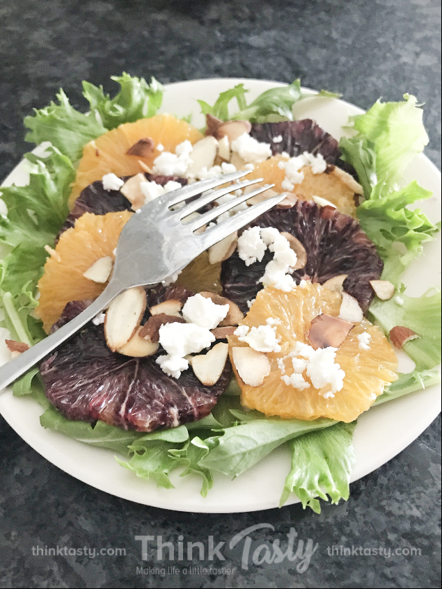 Oranges on a bed of lettuce topped with sliced almonds and feta