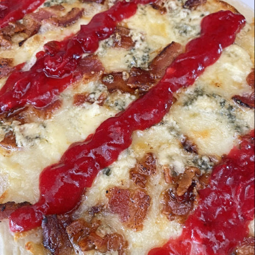 flatbread topped with bacon, blue cheese, and cranberry drizzle